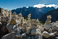Pile of rocks in front of mountain peaks of slovenian Alps at sunny morning near Vrsic mountain pass in Triglav national park Stock Photography