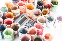 Pile of rolled-up currency notes with a calculator Stock Image