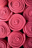 Pile of Rolled up Vibrant Pink Colored Fleece Blankets, Vertical photo for Background Royalty Free Stock Photos