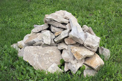 A pile of rough rocks on the green grass Stock Photography