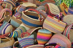Pile of round colorful traditional African woven baskets. At a farmer's market these beautiful multi-colored striped baskets were piled high.  Made of woven Stock Images