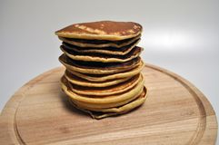 A pile of round golden pancakes on a wooden stand stock image