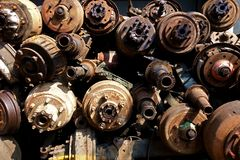 Pile of Rusty Axels and Drive Shafts. Image from an industrial sector or truck graveyard of a stack of old large axels with wheel hubs and vehicle parts Stock Photos