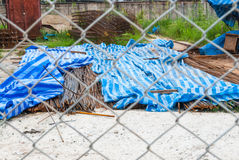 Pile of Rusty Rebars in Construction Site through Metal Mesh Fence Stock Photography