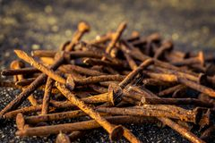 Pile of rusty used nails on the ground focus on the cottonwood s. Eed blur background warm tone color concept image of old age, memories in the past, elder Stock Photo