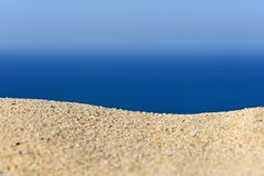 A pile of sand on a beach against the sea and sky Royalty Free Stock Photography