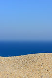 A pile of sand on a beach against the sea and sky Royalty Free Stock Images