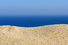 A pile of sand on a beach against the sea and sky Royalty Free Stock Photos
