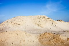 Pile of sand and blue sky over it Stock Images