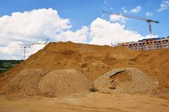 Pile of sand and construction of new homes. Concept for industry. Crane and blue sky with clouds and sun. Building construction si. Te at sunset Stock Images