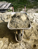 A pile of sand, a shovel and a construction truck for transporta Stock Images