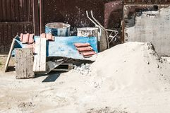 Pile of sand with trolley and other architectural material and tools in front of the residential building constriction site on the stock images