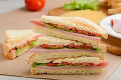Pile of sandwich triangles. Beautiful grill crust and yummy filling of tomato, lettuce, ham and cheese stock images