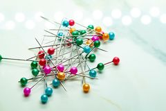 Scattered colorful pins on the marble stock photo
