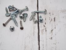 Pile of scattered screws. Concept using screws, or just a picture of the leftover hardware itself. Macro pile of scattered screws in landscape format with room royalty free stock image