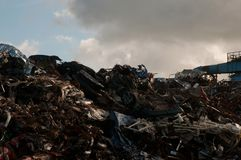 Pile of scrap metal at a junk yard with a metal structure on the side and a cloudy sky in the background. Mountain of scrap metal and metal parts at a landfill stock photo