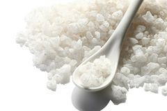 A pile of sea salt with a ceramic spoon on a white background. i Royalty Free Stock Photo