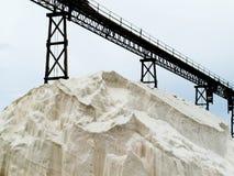 Pile of sea salt under conveyor of saline refinery Royalty Free Stock Photos