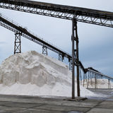 Pile of sea salt under conveyor of saline refinery Royalty Free Stock Photo