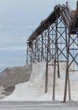 Pile of sea salt under conveyor of saline refinery Royalty Free Stock Image
