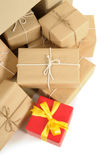 Pile of several brown paper parcels and single unique small red christmas gift, white background Royalty Free Stock Photography