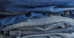 Pile of shabby denim clothing. A few jeans close-up Stock Images