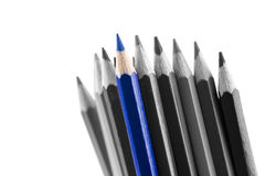 Pile of sharp colored pencils, with different hues. From black to light grey and a blue outstanding one, close-up on white background Royalty Free Stock Images