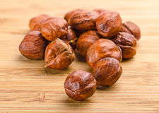 A pile of shell-less hazelnuts,  on textural wood backgr Royalty Free Stock Photos