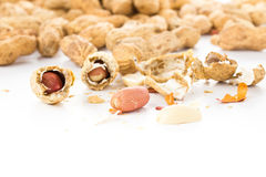 A pile of shelled big peanuts with some cracked open on white ba Royalty Free Stock Image
