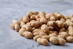 Pile of shelled peanuts on white background, top view, close-up, vertical, shallow depth of field. Pile of shelled peanuts on white textured background, close-up royalty free stock photography