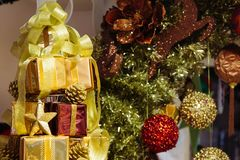Pile of shiny gift boxes decorated in Christmas tree with Christmas ornament decorations in the background. Pile of shiny gift boxes decorated in Christmas tree Royalty Free Stock Image