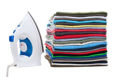 Pile of shirts and iron on the left. Isolated on a white background Royalty Free Stock Images