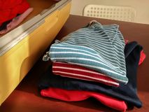 Pile of shirts on table next to suitcase. This is a picture of a suitcase being packed. The suitcase is on a wooden table, with a pile of clothes on the table Royalty Free Stock Photography
