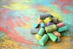 Pile of Sidewalk Chalk. A collection of colorful sidewalk chalk is piled up on a rainbow drawing, outside on the pavement Royalty Free Stock Image