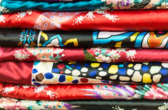Pile of silk clothes with abstract asian design. Royalty Free Stock Images