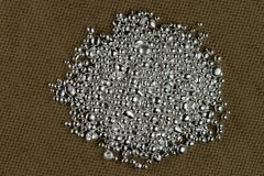 A pile of silver grains on the background to the coarse texture of the textile royalty free stock photography