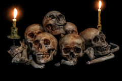 Pile of skulls and bones with two candles Royalty Free Stock Images