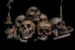 Pile of skulls and bones with two candles and smoke Royalty Free Stock Image