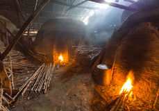Pile of slow burning wood at charcoal factory, Thailand Royalty Free Stock Photography