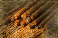 Pile of small cigar on old wooden table overlap with old wall Royalty Free Stock Image