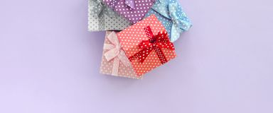 Pile of a small colored gift boxes with ribbons lies on a violet background. Minimalism flat lay top view.  stock photography