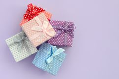 Pile of a small colored gift boxes with ribbons lies on a violet background. Minimalism flat lay top view.  royalty free stock photography