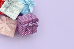 Pile of a small colored gift boxes with ribbons lies on a violet background. Minimalism flat lay top view.  stock image