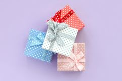 Pile of a small colored gift boxes with ribbons lies on a violet background. Minimalism flat lay top view.  stock photo
