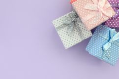 Pile of a small colored gift boxes with ribbons lies on a violet background. Minimalism flat lay top view.  stock images