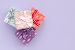 Pile of a small colored gift boxes with ribbons lies on a violet background. Minimalism flat lay top view.  stock photos