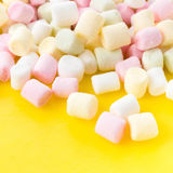 A pile of small colored puffy marshmallows  on bright yellow  ba. A pile of small colored puffy marshmallows  on bright yellow colored   background close up, top Stock Photo