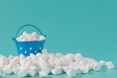 Pile of small puffy marshmallows on aquamarine background close Stock Image