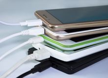 Recharging smartphones and tablets. A pile of smartphones, charging through usb cables royalty free stock photography