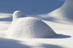 Pile of snow in bright sunlight. With blue shadows royalty free stock photo